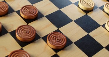wooden pieces set up on a checkers game board
